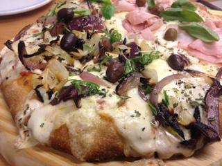 Pizza de Picsa en Madrid. Dos coberturas en una. Cebolla y aceitunas, por un lado y jamón y queso con albahaca por otro